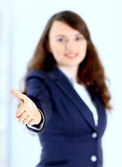 Una bella giovane donna d'affari sorridente, felice e sorridente, con una mano aperta pronta a sigillare un accordo o a dire benvenuto. isolato su uno sfondo bianco.