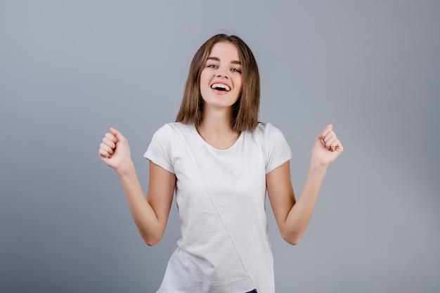 Bello giovane dancing sorridente della ragazza con le mani isolate sopra grey