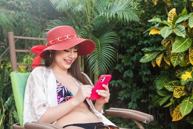 Bella ragazza sorridente che fa una videochiamata sul suo smartphone nel suo cortile