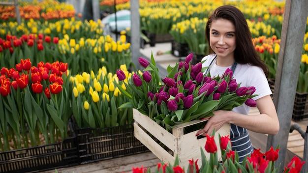 Bella giovane ragazza sorridente, lavoratore con fiori in serra. concetto di lavoro in serra, fiori.