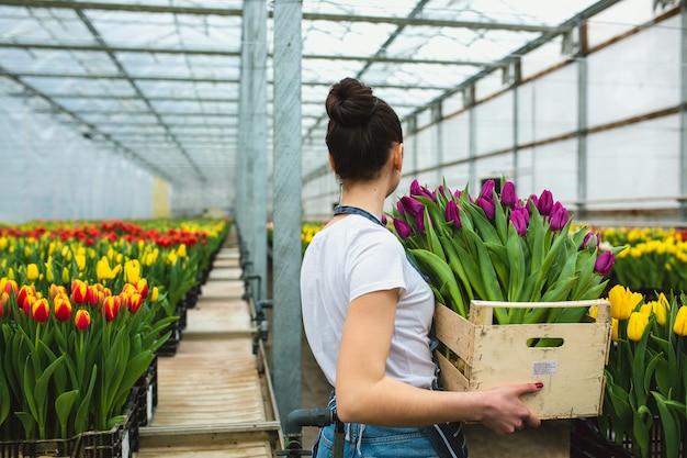 Bella giovane ragazza sorridente, lavoratore con fiori in serra vista dal retro. concetto di lavoro in serra, fiori.