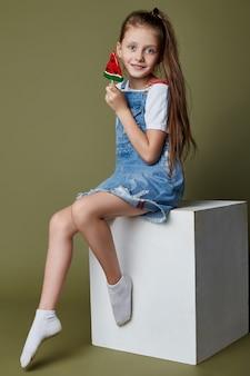 Bella giovane ragazza teenager sorridente che tiene un lecca-lecca sotto forma di una fetta di anguria. emozioni gioiose allegre sul viso della ragazza