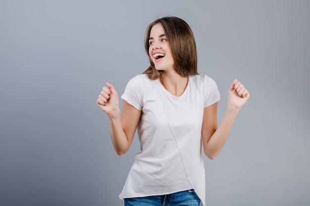 Bello giovane dancing sorridente della donna con le mani isolate sopra grey