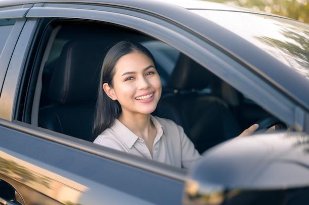 Una bella giovane donna sorridente che guida il suo concetto di automobile, assicurazione e finanza