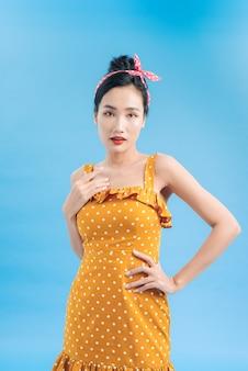 Bella giovane donna sorridente che indossa il vestito a pois.