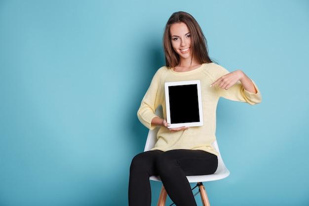 Bella giovane ragazza sorridente che indica lo schermo vuoto isolato sullo sfondo blu