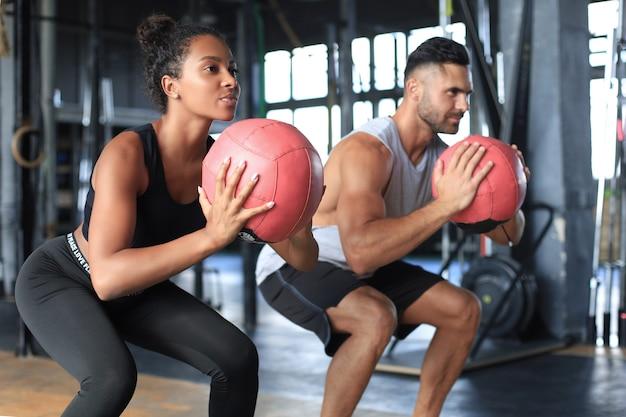Bella giovane coppia sportiva sta lavorando con la palla medica in palestra.