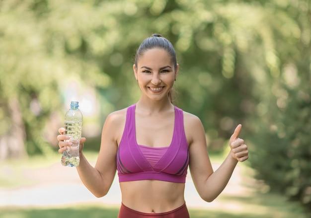 Bella giovane sportiva sorridente dopo l'allenamento con una bottiglia d'acqua in mano