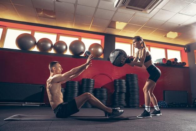 Bella giovane coppia sportiva allenamento allenamento in palestra insieme gym