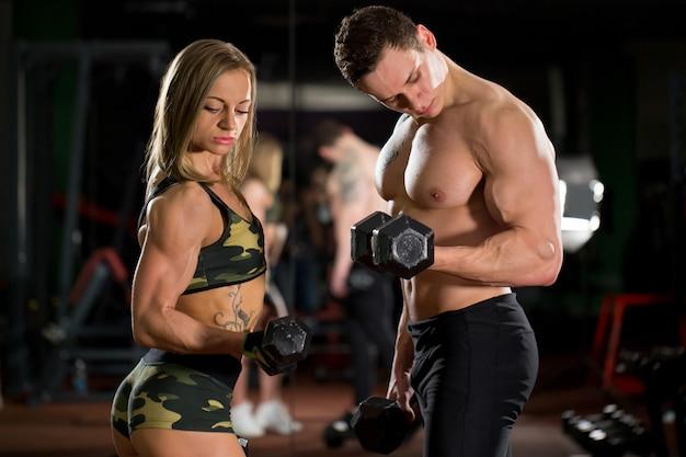 Belle giovani coppie sexy sportive che mostrano muscolo e allenamento in palestra