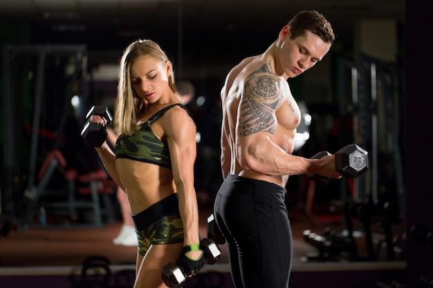 Belle giovani coppie sexy sportive che mostrano muscolo e allenamento in palestra Foto Premium