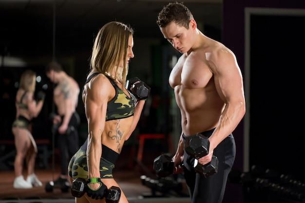 Bella giovane coppia sexy sportiva che mostra muscoli e allenamento in palestra