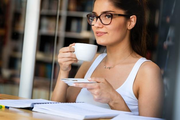 Bella giovane studentessa con tanti libri, che studia o si prepara per gli esami