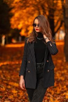 Bella giovane donna d'affari alla moda con occhiali da sole alla moda in un abito nero alla moda con un blazer elegante e un maglione cammina in un parco autunnale con fogliame dorato colorato