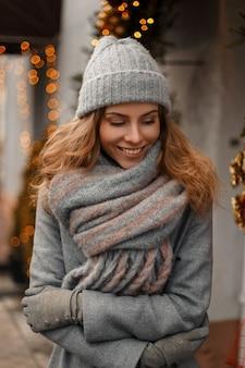 Bella giovane ragazza alla moda sorride in vestiti grigi lavorati a maglia inverno alla moda in vacanze invernali sulla strada vicino alle luci