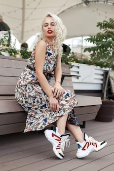 Bella giovane ragazza alla moda in abito di moda vintage con un motivo seduto su una panca di legno in città