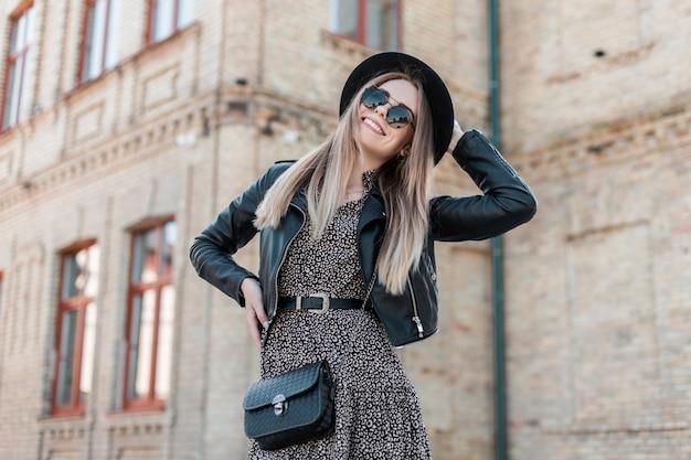 La bella giovane donna alla moda dei pantaloni a vita bassa in un vestito casuale alla moda con un cappello e gli occhiali da sole cammina nella città