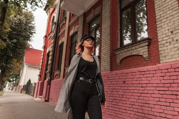 Bella giovane adolescente alla moda in abiti alla moda cammina per strada vicino a un edificio d'epoca