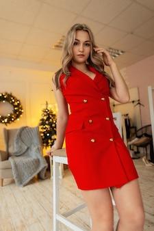 Bella giovane donna elegante in abiti eleganti rossi alla moda vicino a una sedia sullo sfondo di un albero di natale e luci gialle