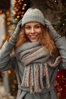Bella giovane donna alla moda in vestiti lavorati a maglia alla moda in un cappotto grigio con un cappello e una sciarpa alla moda in città durante le vacanze invernali vicino alle luci