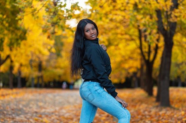 Bella giovane donna alla moda con la pelle nera in abiti alla moda con una giacca e jeans blu cammina in un parco autunnale con foglie autunnali di colore giallo brillante