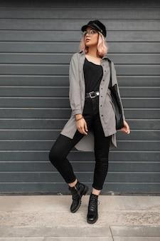 La bella giovane donna alla moda con gli occhiali e un cappello vintage in abiti casual alla moda con una camicia e jeans si trova vicino al cancello sulla strada