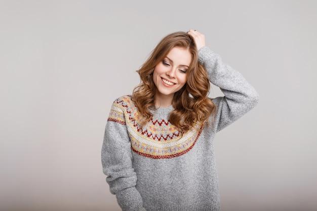 Bella giovane donna alla moda con un sorriso in un maglione grigio vintage in studio