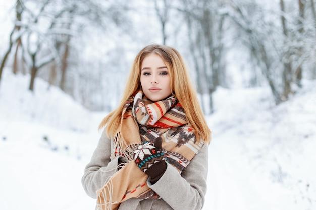 Bella giovane donna alla moda con una sciarpa di lana vintage in un cappotto elegante con guanti caldi