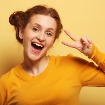 Bella giovane donna sorpresa del redhair su colore giallo