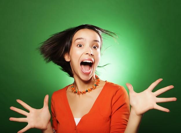 Bella giovane donna sorpresa su sfondo verde