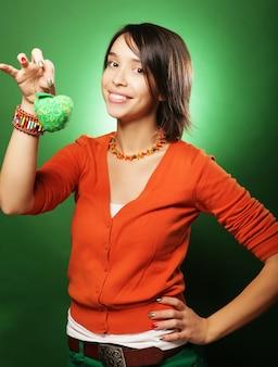 Bella giovane donna sorpresa sopra il muro verde