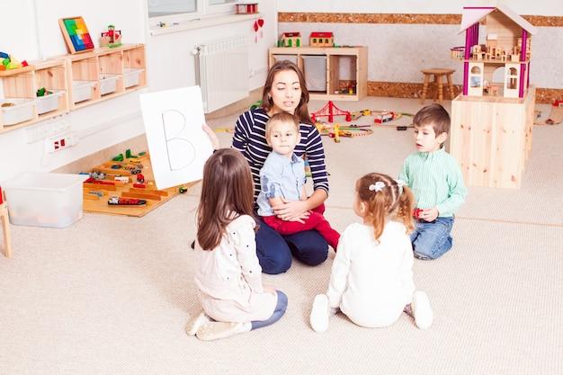 Bella giovane insegnante che mostra la lettera ai bambini in età prescolare, i bambini si siedono in cerchio