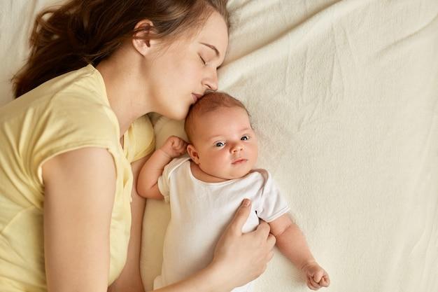 Bella giovane mamma addormentata stanca vicino al bambino sdraiato sul letto sulla coperta bianca, neonato guarda la telecamera, mamma che bacia la figlia o il figlio. maternità.