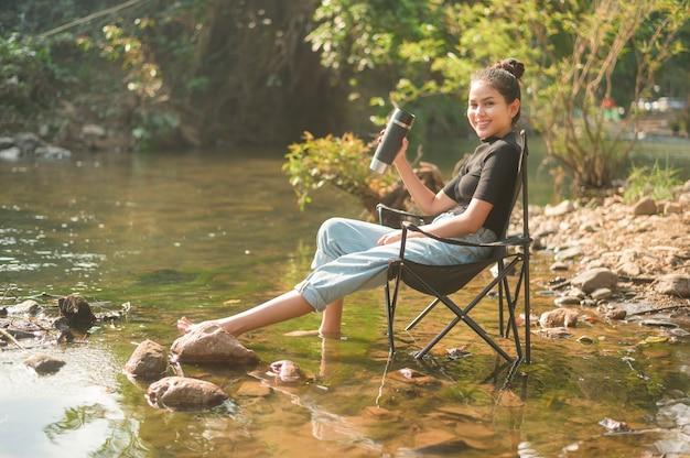 Una bella giovane donna viaggiatrice si sta godendo la natura bevendo caffè al mattino sul lago, relax, vacanza in campeggio e concetto di viaggio.