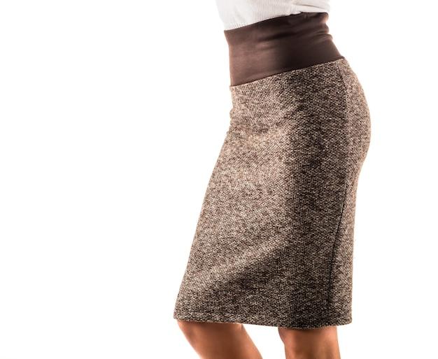 Bella giovane donna non identificata in una gonna marrone stretta e un top in maglia bianca di lana in posa su un muro bianco