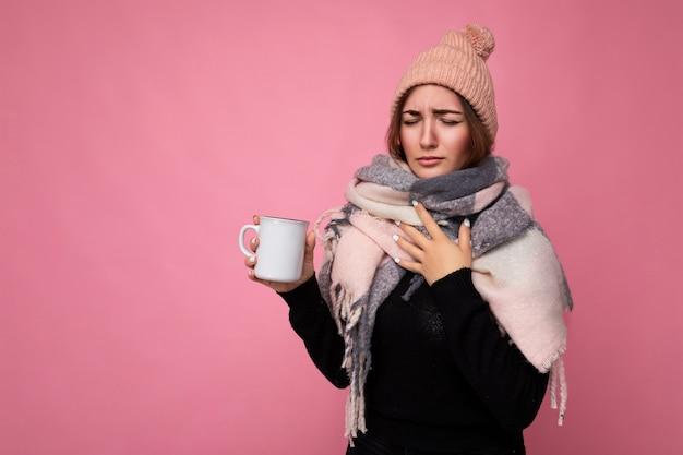 Bella giovane donna bruna sconvolta che indossa un maglione nero e una sciarpa calda isolata sopra il rosa