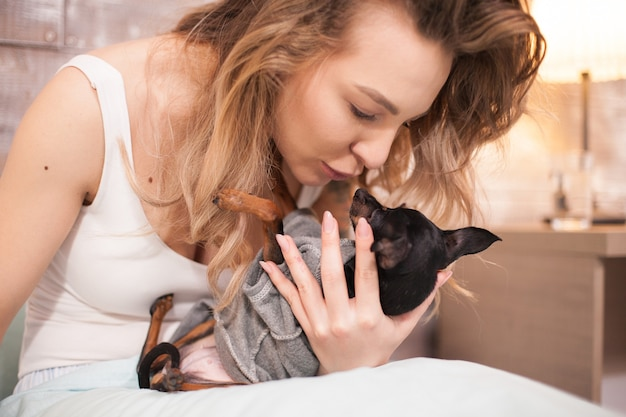 Bella giovane pigiama da portare che bacia il suo cagnolino. bella donna.