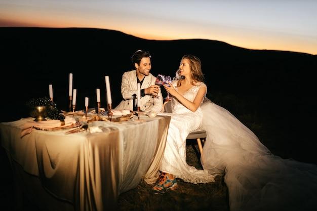 Bella giovane coppia di sposi sorridente matrimonio serale in montagna a un tavolo per due