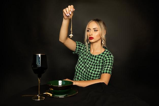 Bella giovane strega con rossetto rosso sulle labbra e trucco evoca su sfondo nero, rituale magico per la ricchezza. foto in studio