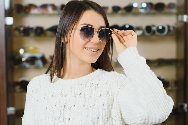 Bella giovane donna che adegua i suoi nuovi occhiali da sole in piedi nel negozio di ottica