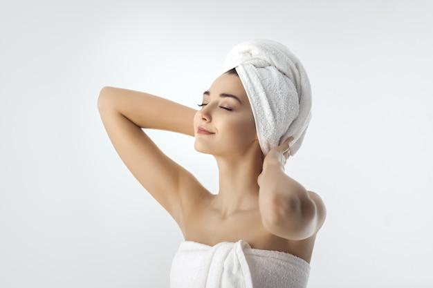 Bella giovane donna dopo il bagno su bianco