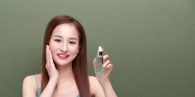 Bella giovane donna che si applica il siero sulla pelle su uno sfondo colorato