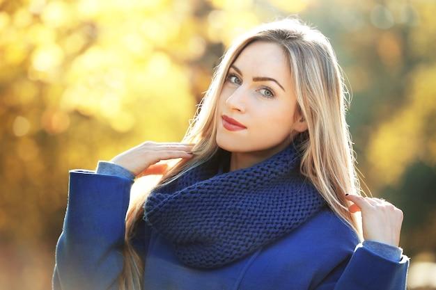 Bella giovane donna nella sosta di autunno il giorno pieno di sole