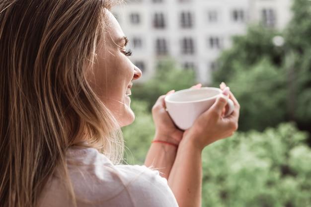 Bella giovane donna su un balcone che gode mattina con una tazza di tè