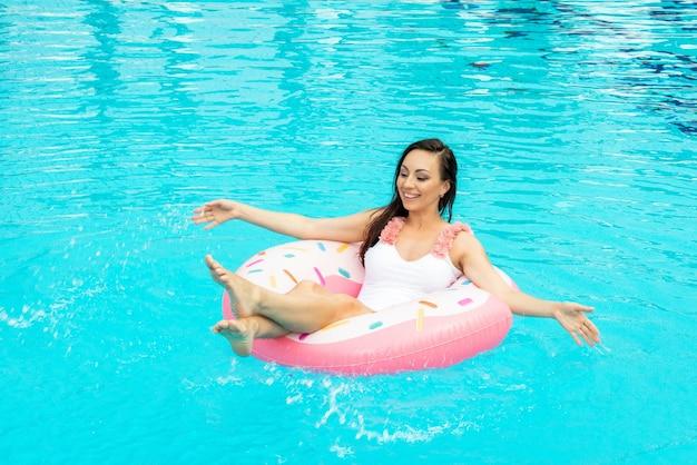 Bella giovane donna in costume da bagno rilassante sulla ciambella gonfiabile in piscina.