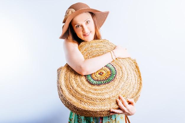 Bella giovane donna in prendisole cappello da spiaggia che abbraccia una borsa da spiaggia in rattan. concetto di amore per la spiaggia estiva