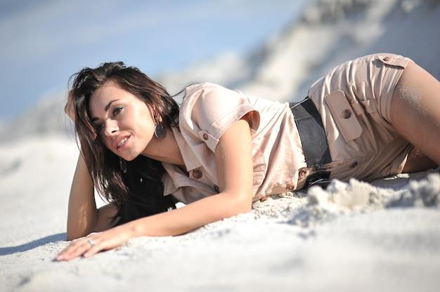 Bella giovane donna in abiti estivi biege sulla sabbia