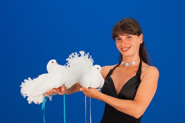 La bella giovane donna in vestito nero sorride e tiene un paio di piccioni bianchi, copyspace.