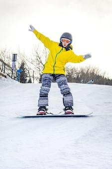 La bella giovane donna in casco nero e giacca gialla impara a fare snowboard