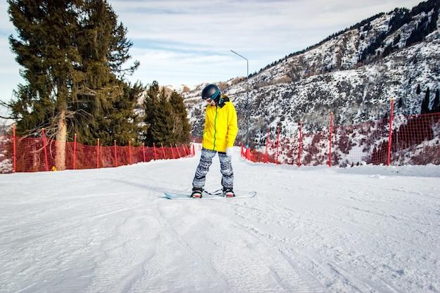La bella giovane donna in casco nero e giacca gialla impara a cavalcare lateralmente sullo snowboard